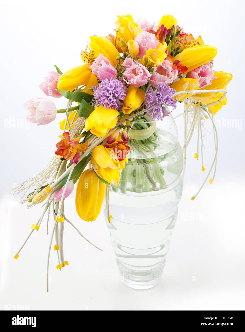 Colorful festive bouquet of spring flowers in glass vase over white ...