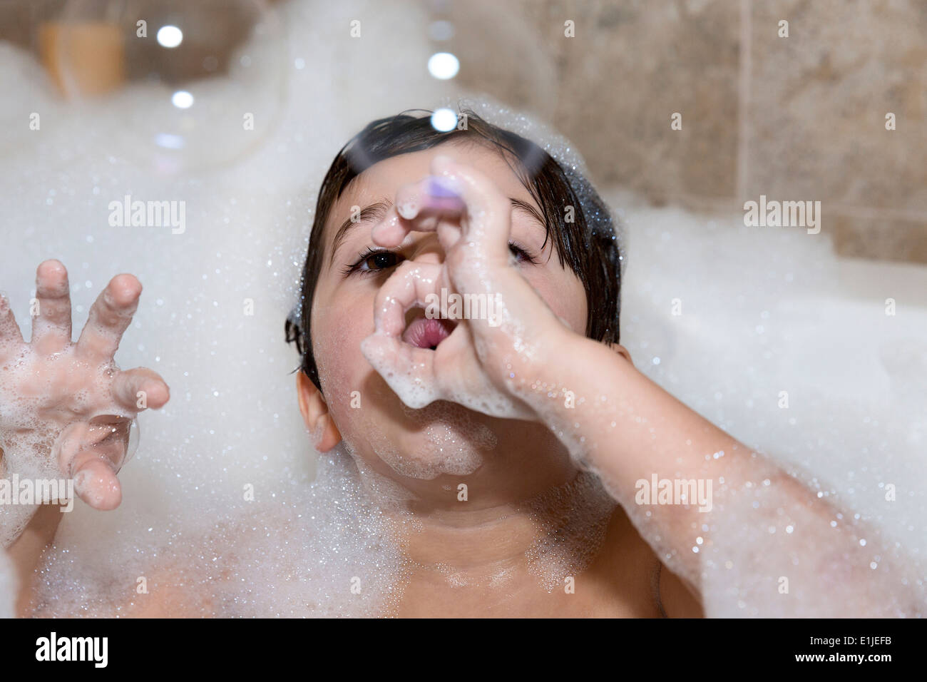 Young boy blowing bubbles in bubble bath - Stock Image