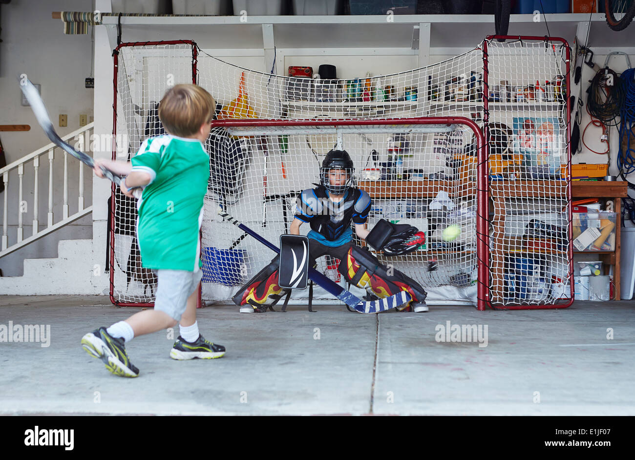 Boys playing hockey in garage - Stock Image