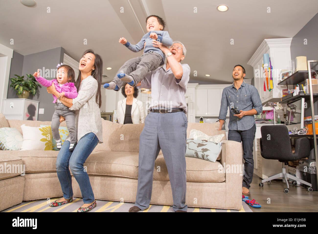Three generation family having fun in sitting room - Stock Image