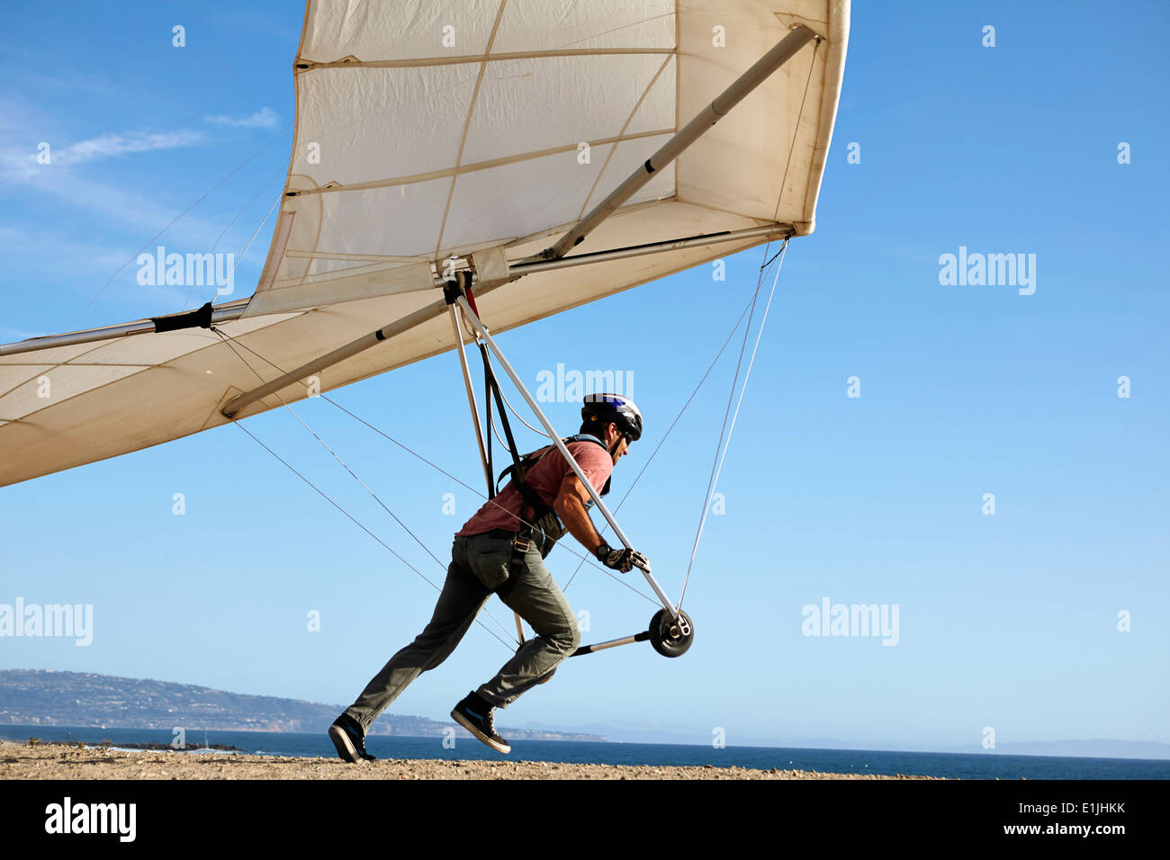 Hang glider pilot taking off - Stock Image