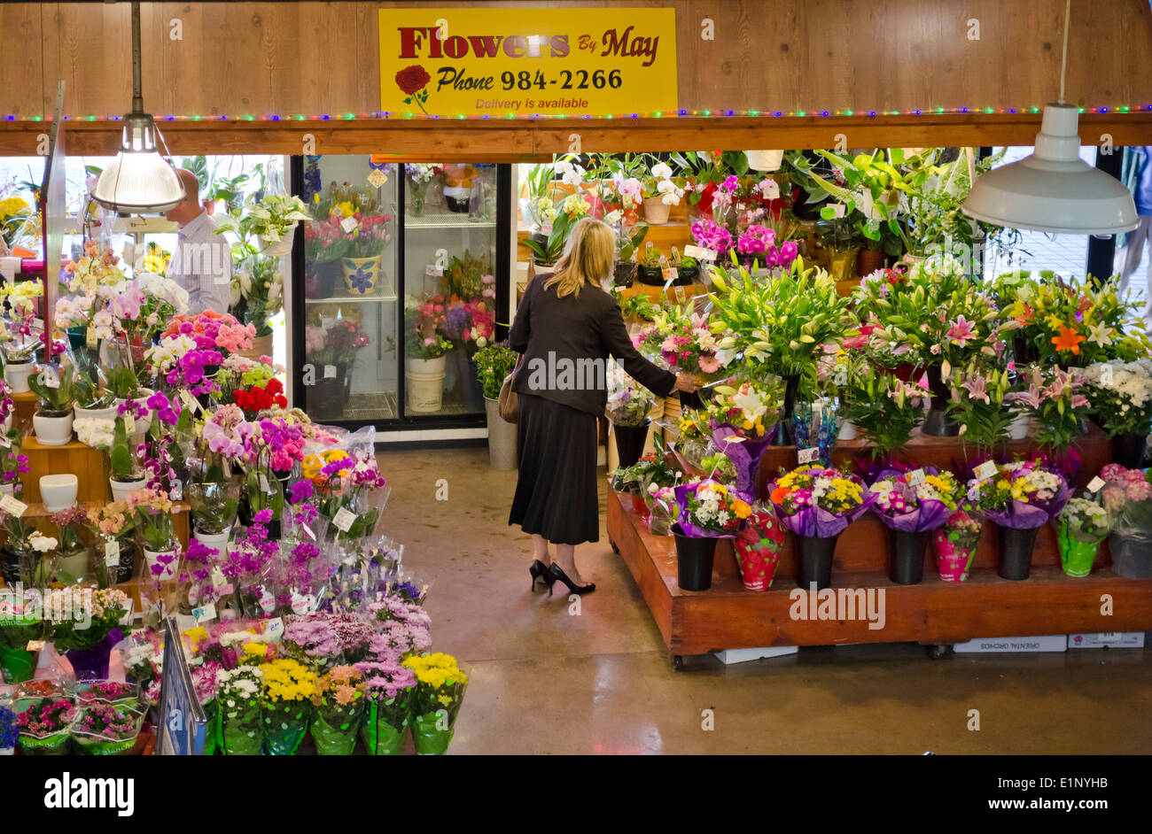 Woman choosing a bouquet at a flower shop (Flowers by May) in Stock ...