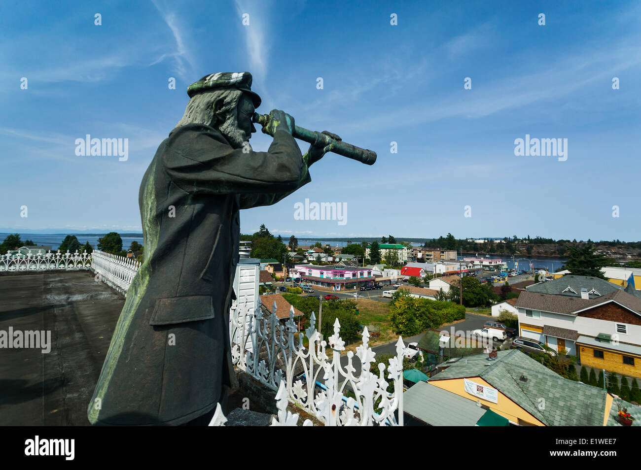 A bronze statue seafaring history keeps a watch out over the town Chemainus high atop a building.  Chemainus Vancouver - Stock Image