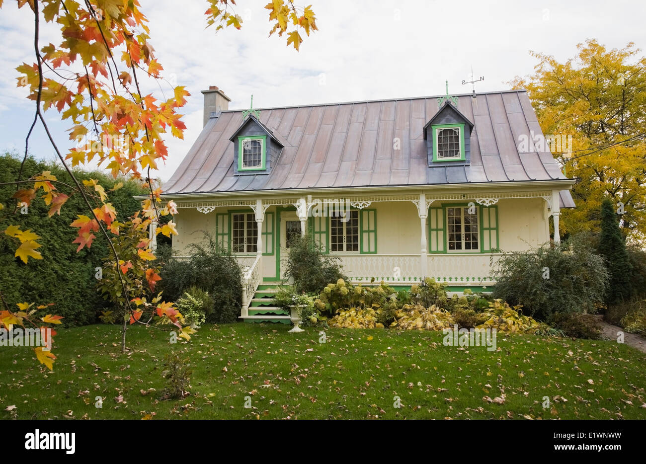 Old reconstructed (1977) Canadiana cottage style residential log home in autumn Quebec Canada. This image is property - Stock Image
