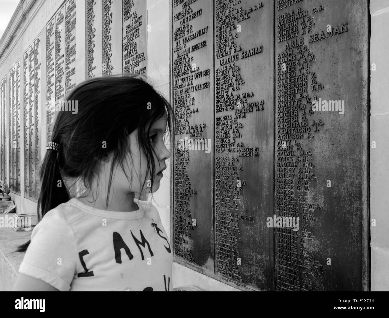 a-young-girl-reads-the-list-of-names-on-the-royal-navy-war-memorial-E1XC74.jpg
