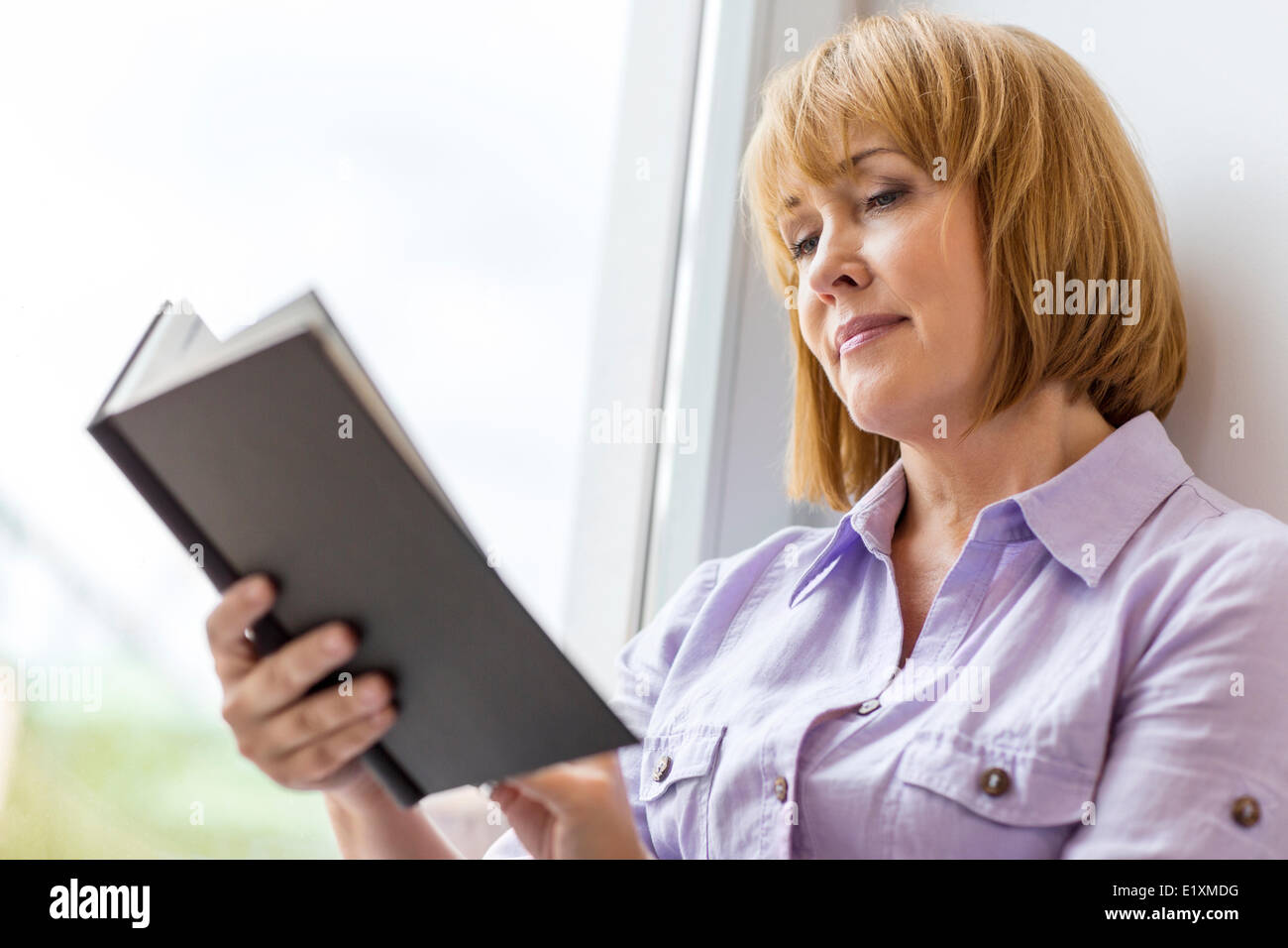 Mature woman reading book by window at home - Stock Image