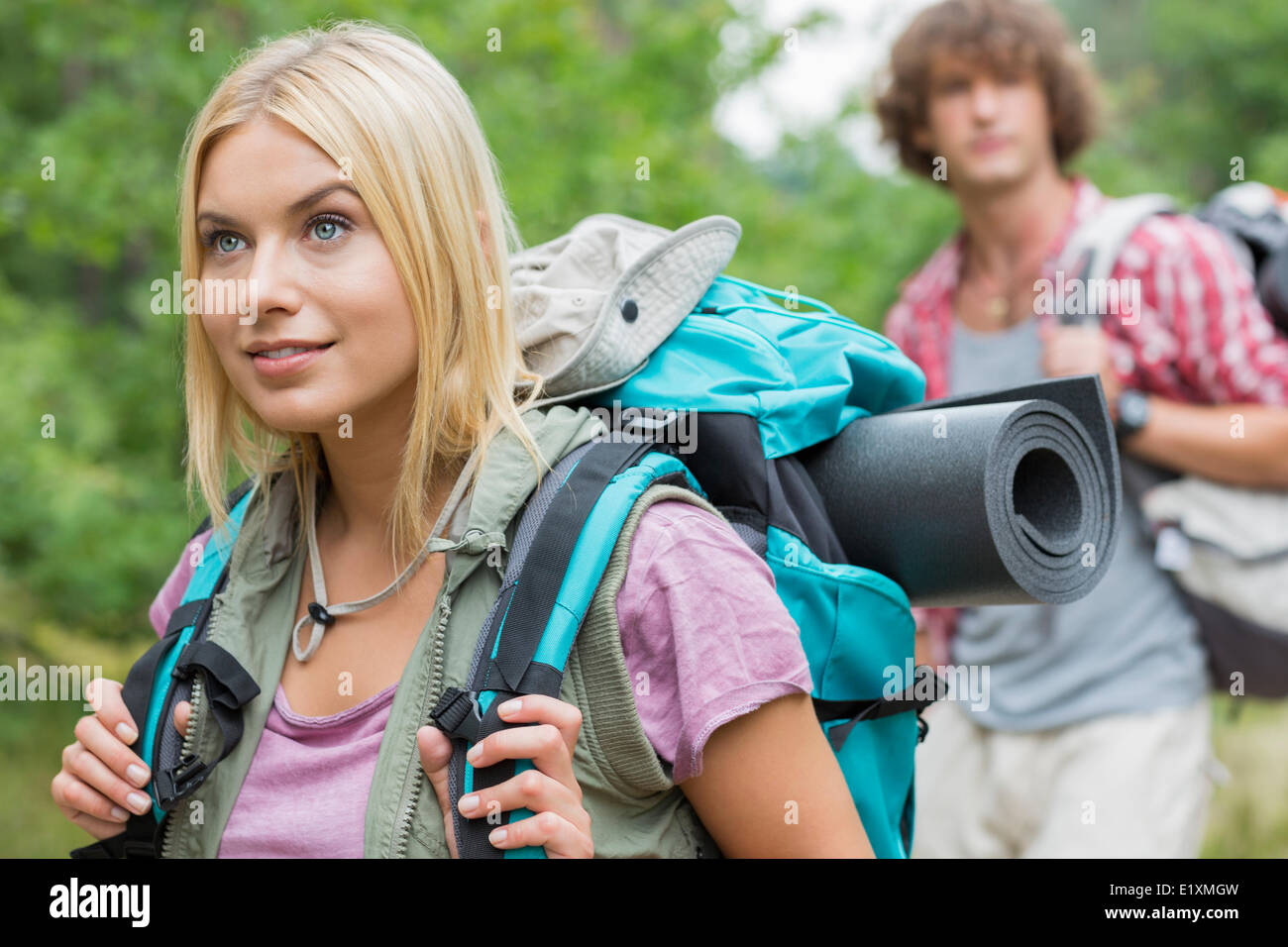 Beautiful female backpacker looking away with man in background at forest - Stock Image
