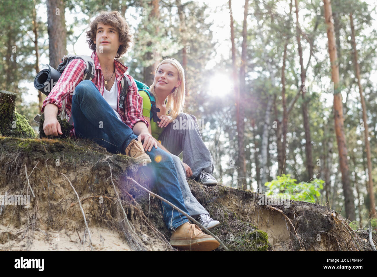 Young hiking couple sitting on edge of cliff in forest - Stock Image