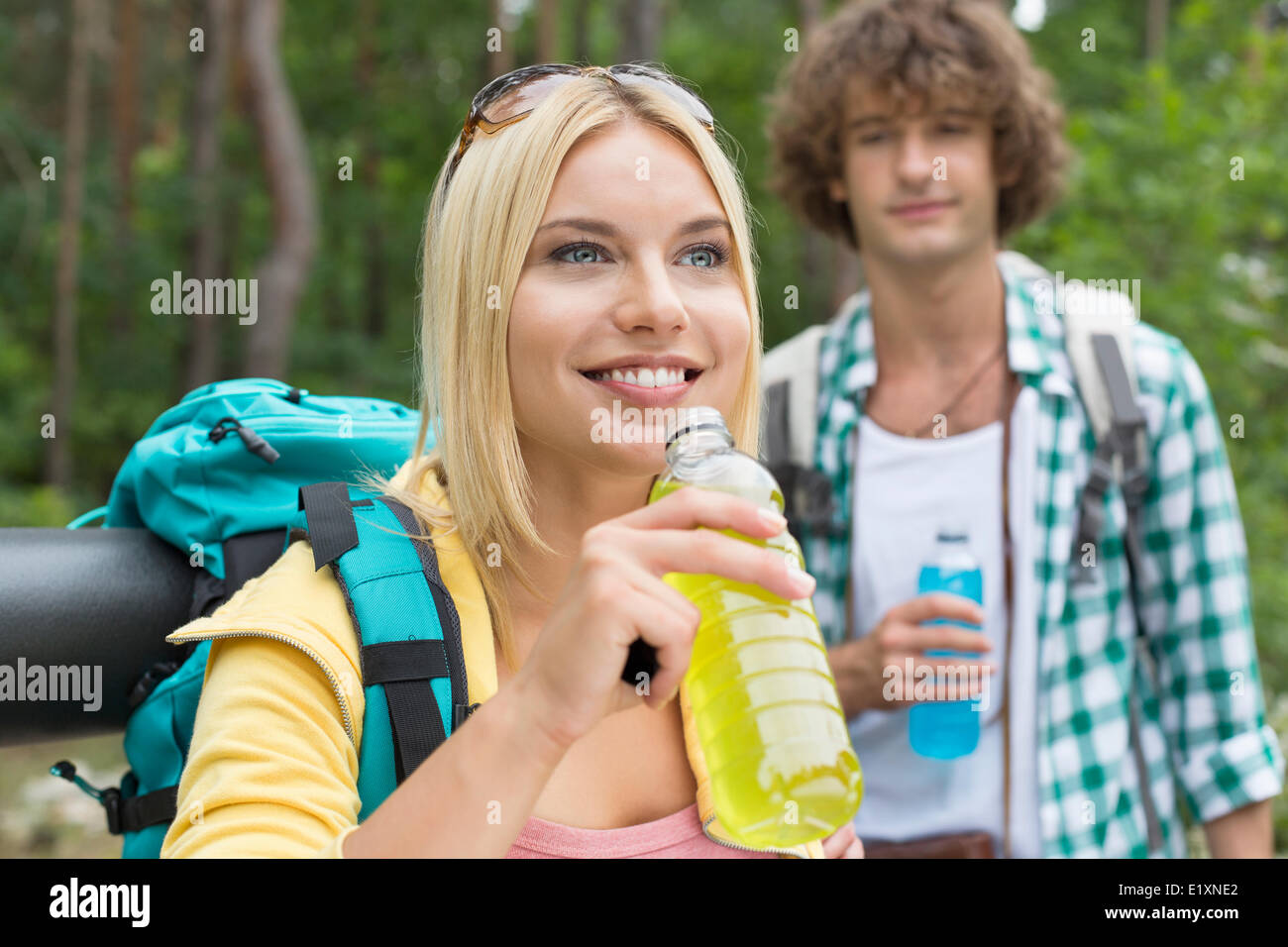 Hiking couple with energy drinks in forest - Stock Image