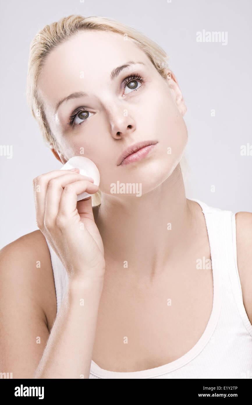 Beautiful blonde removing facial make-up - Stock Image