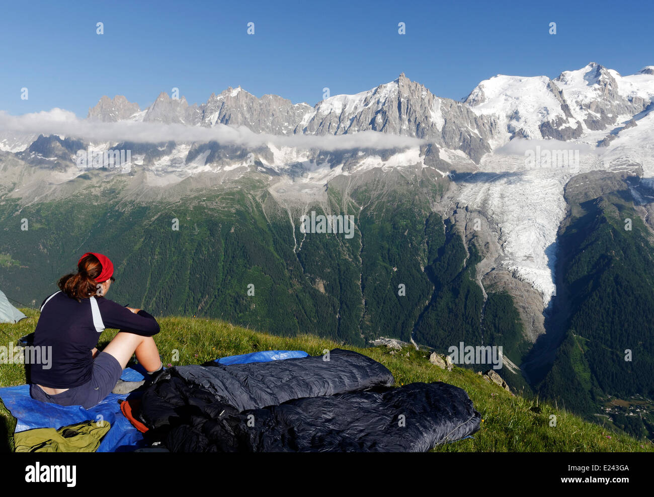 A woman admires the view wild camping on le Brevent  in the French Alps with the Mont Blanc massif beyond Stock Photo