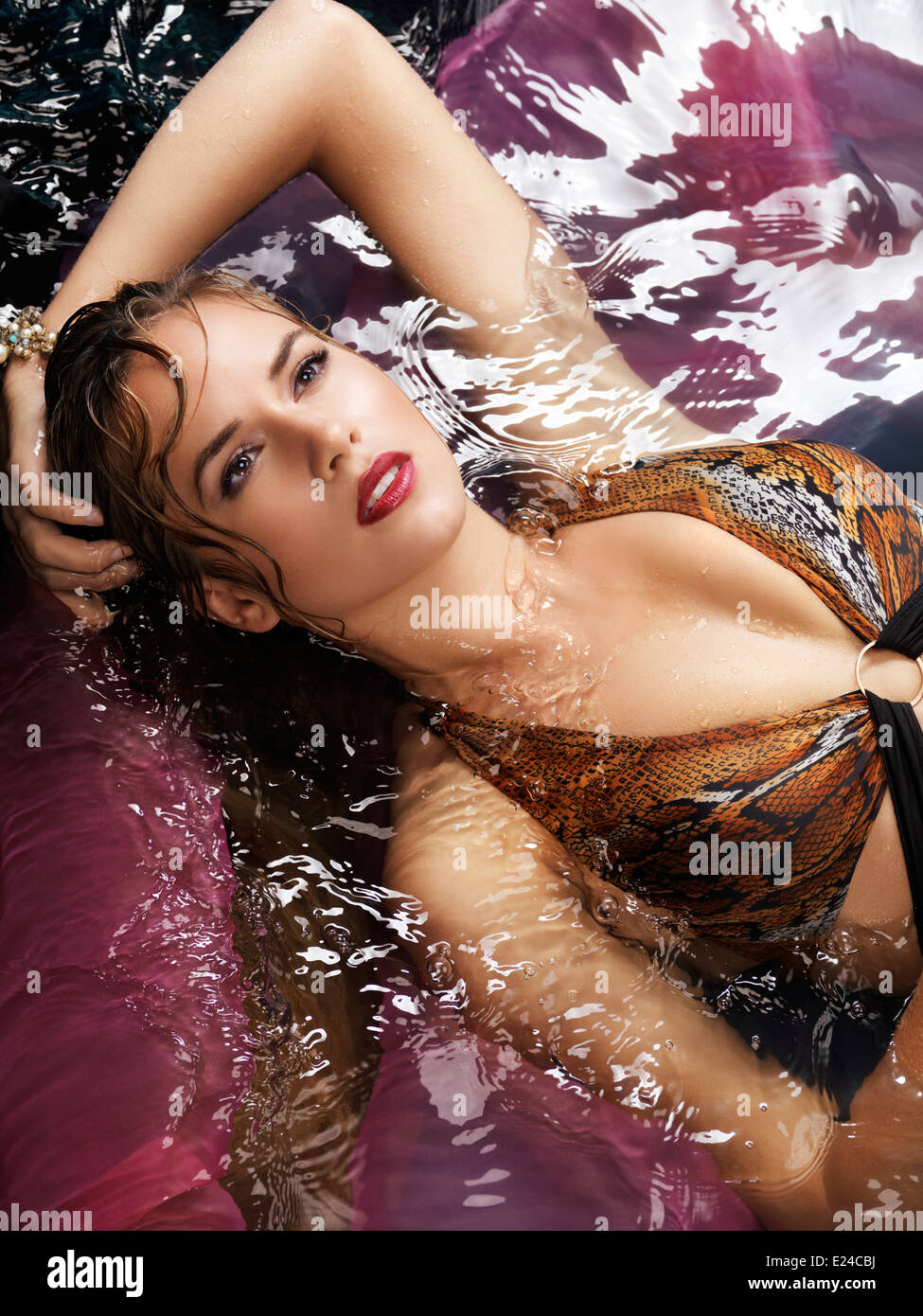 Beauty portrait of a young woman in a swimsuit lying in water - Stock Image