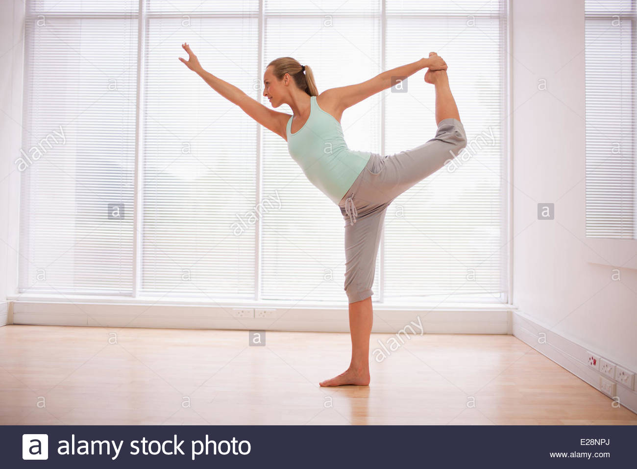 Portrait of smiling woman stretching in fitness studio - Stock Image
