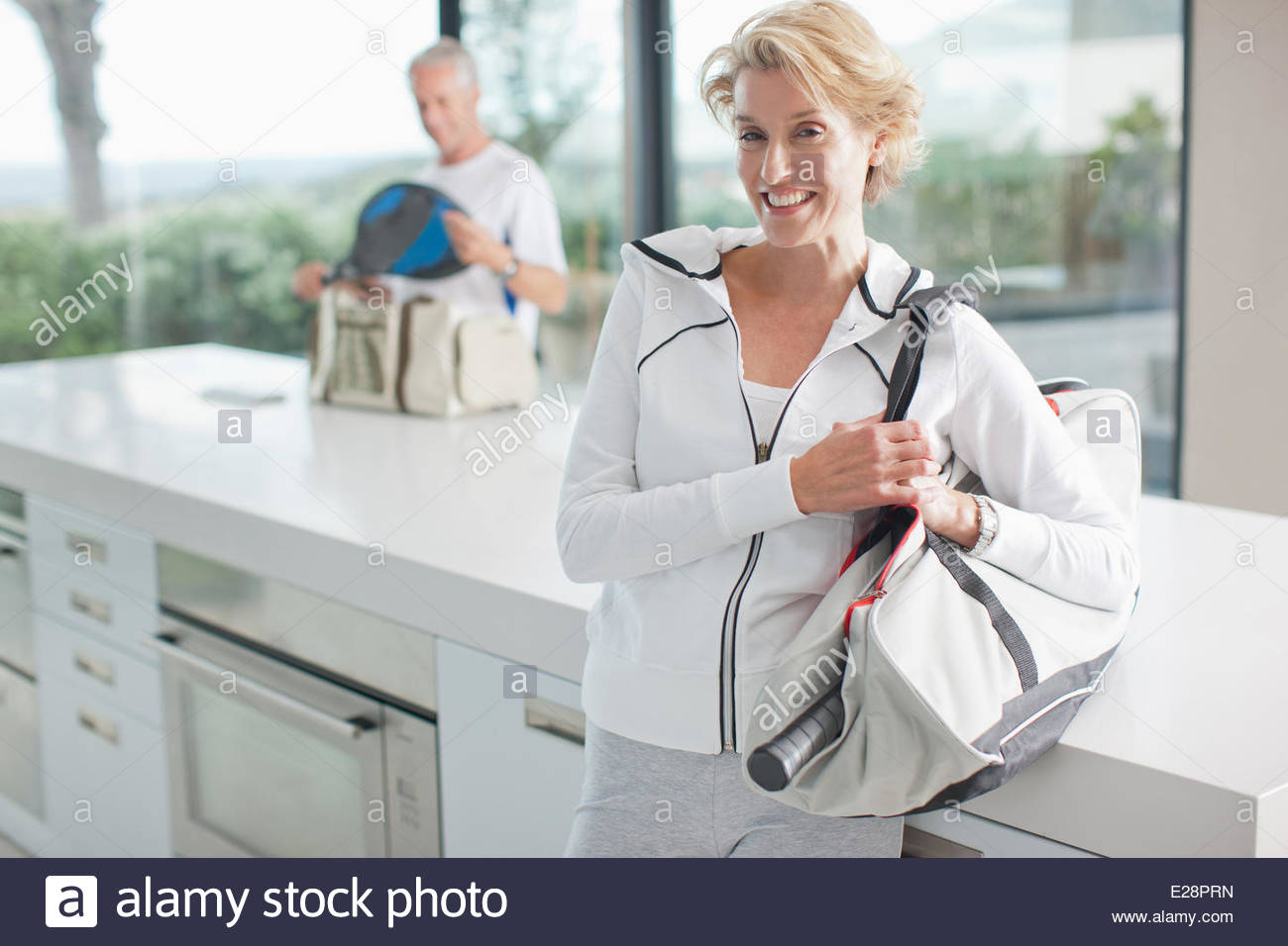 Woman carrying tennis racquet in gym bag - Stock Image