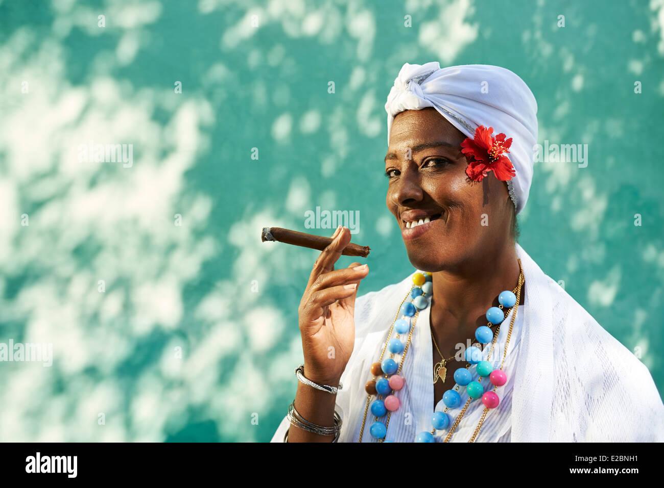 Portrait of african cuban woman smoking cohiba cigar and looking at camera smiling - Stock Image