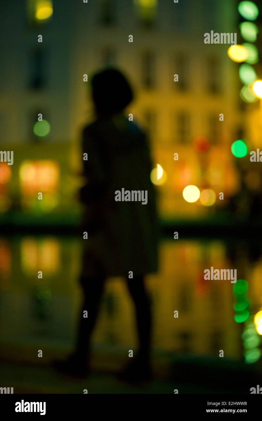 Woman walking at night along urban riverside - Stock Image