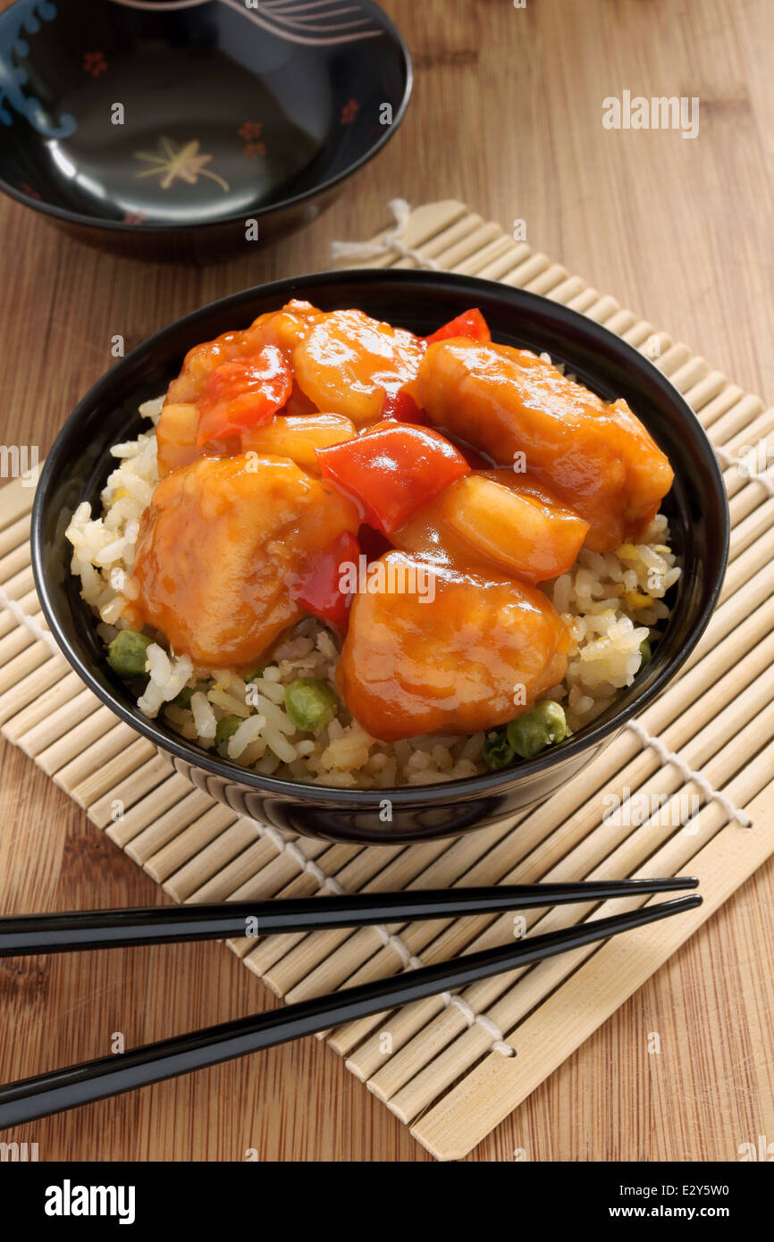 Sweet and sour chicken Cantonese style with egg fried rice in a lacquer bowl with chopsticks Stock Photo