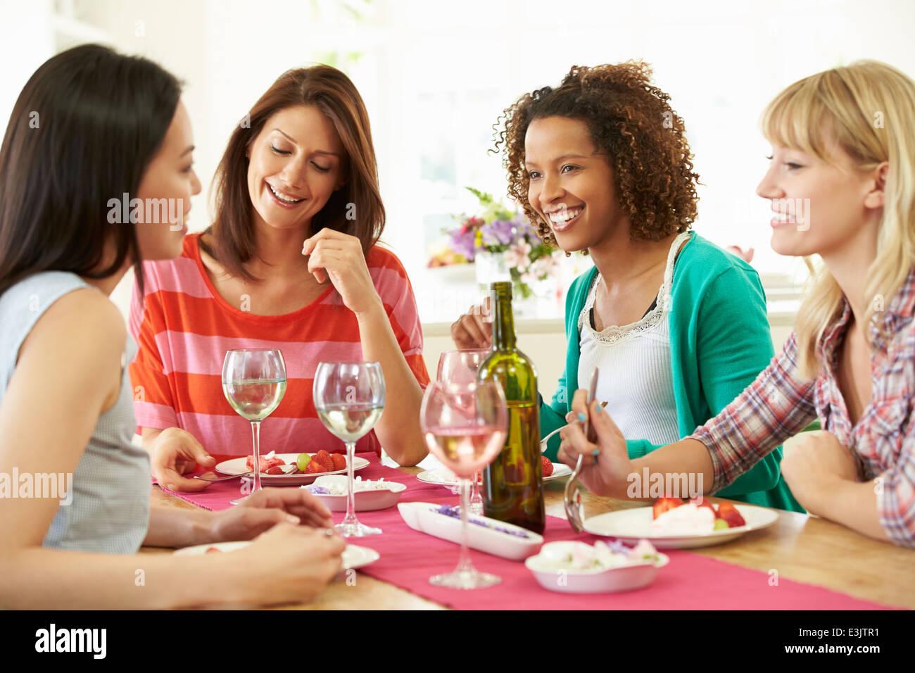 Group Of Women Sitting Around Table Eating Dessert - Stock Image