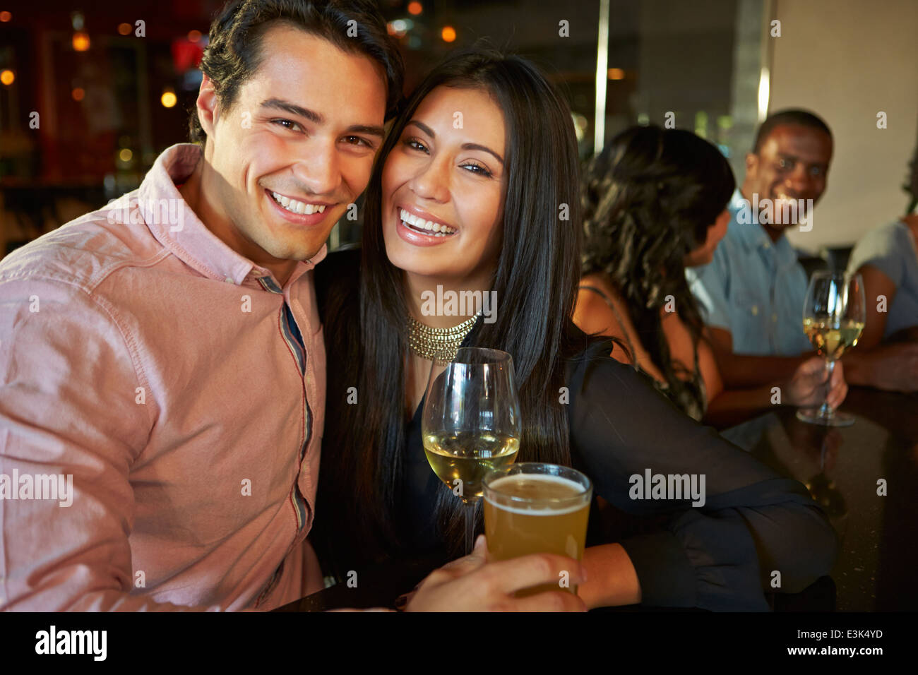 Couple Enjoying Drink At Bar With Friends - Stock Image