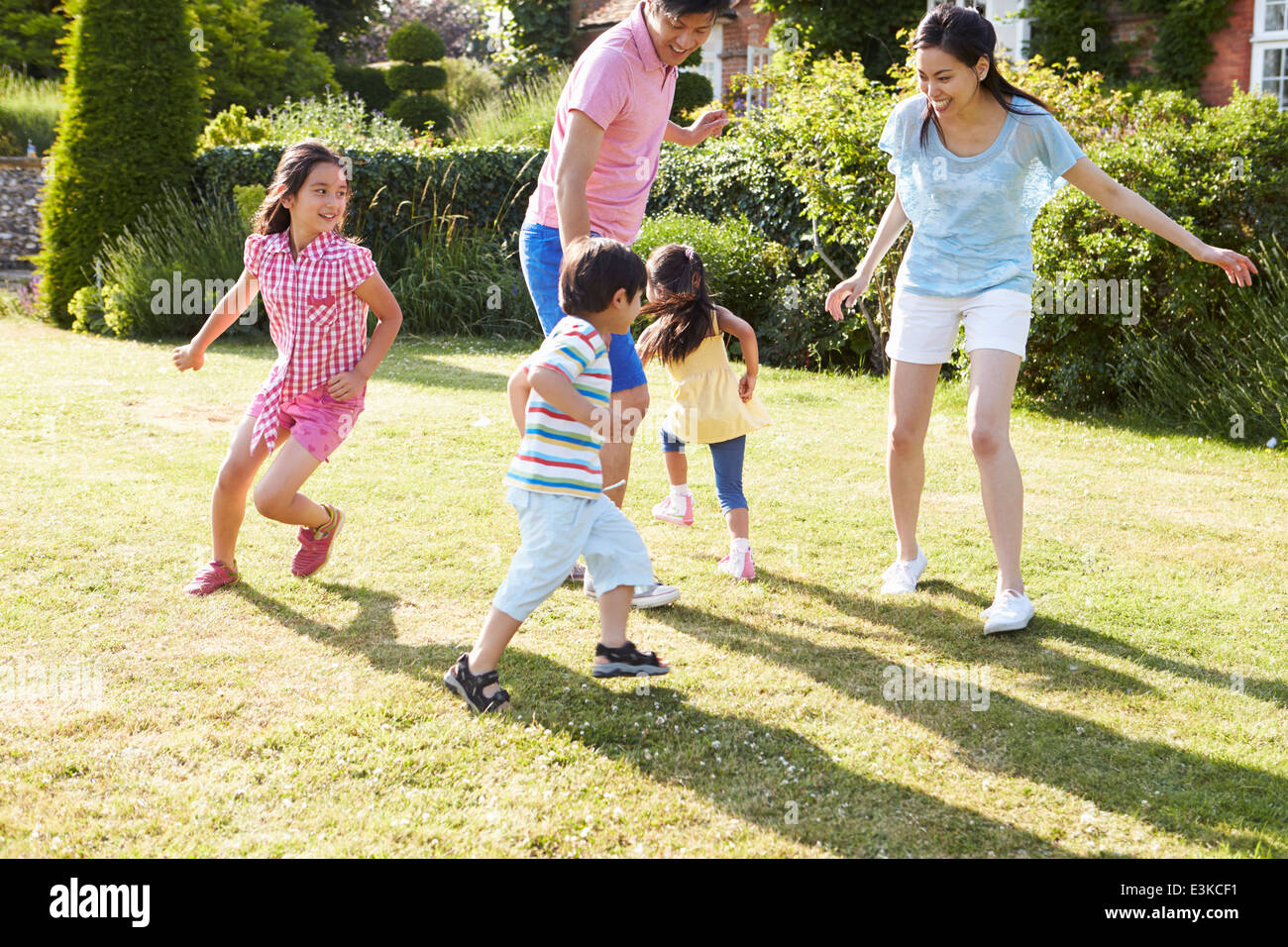 Asian Family Playing In Summer Garden Together - Stock Image