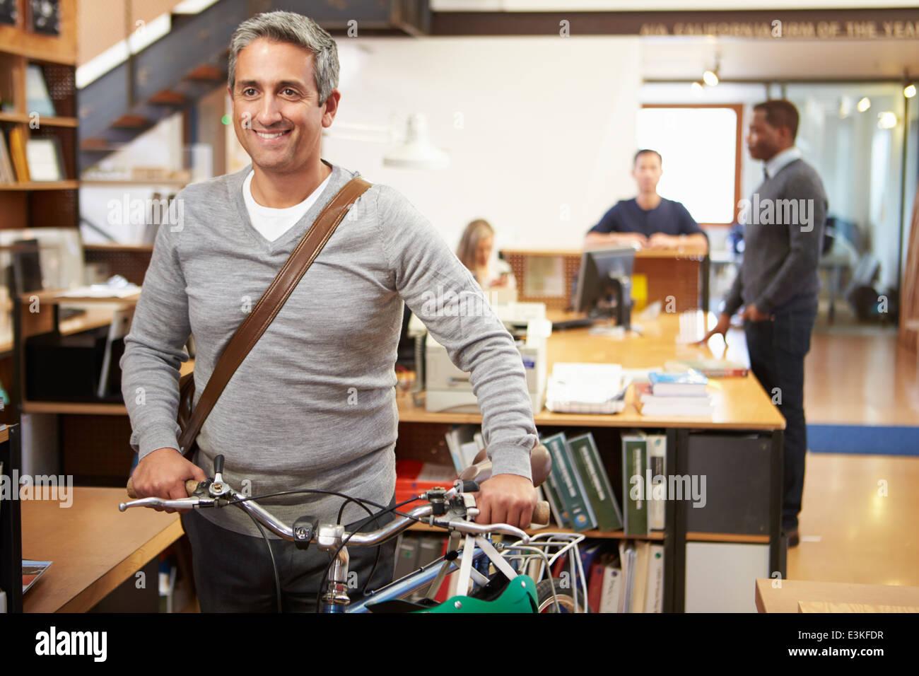 Architect Arrives At Work On Bike Pushing It Through Office - Stock Image