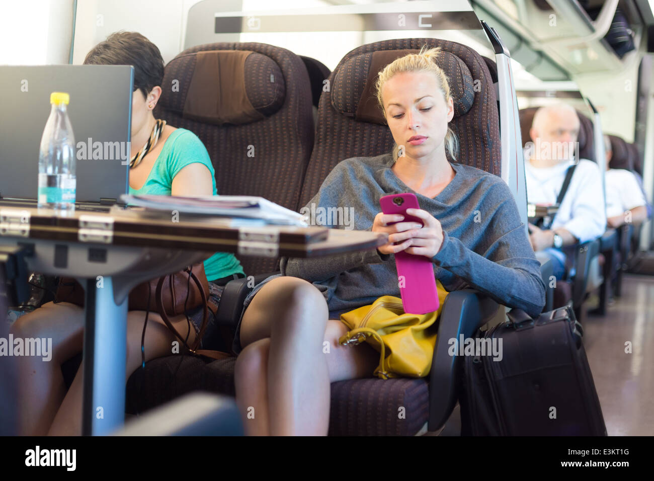 Lady traveling by train using smartphone. - Stock Image