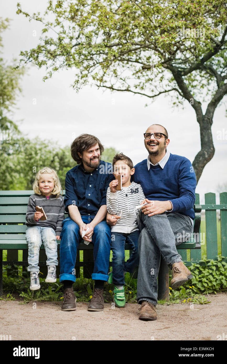 Happy male homosexual family spending leisure time at park - Stock Image