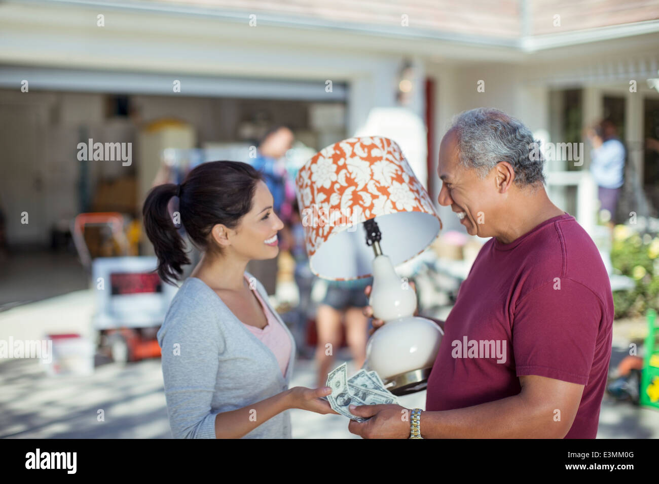 Man buying lamp at yard sale - Stock Image