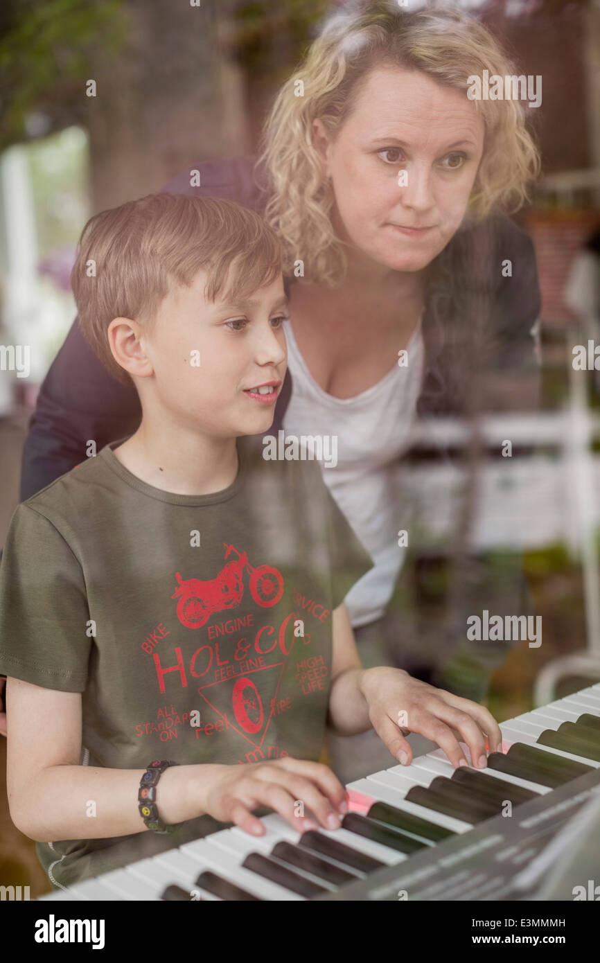 Mother teaching piano to son in house - Stock Image