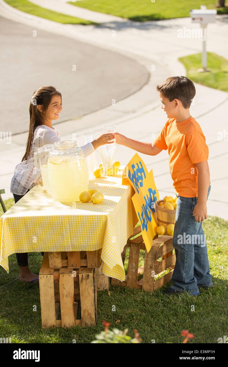 Boy buying lemonade at lemonade stand - Stock Image