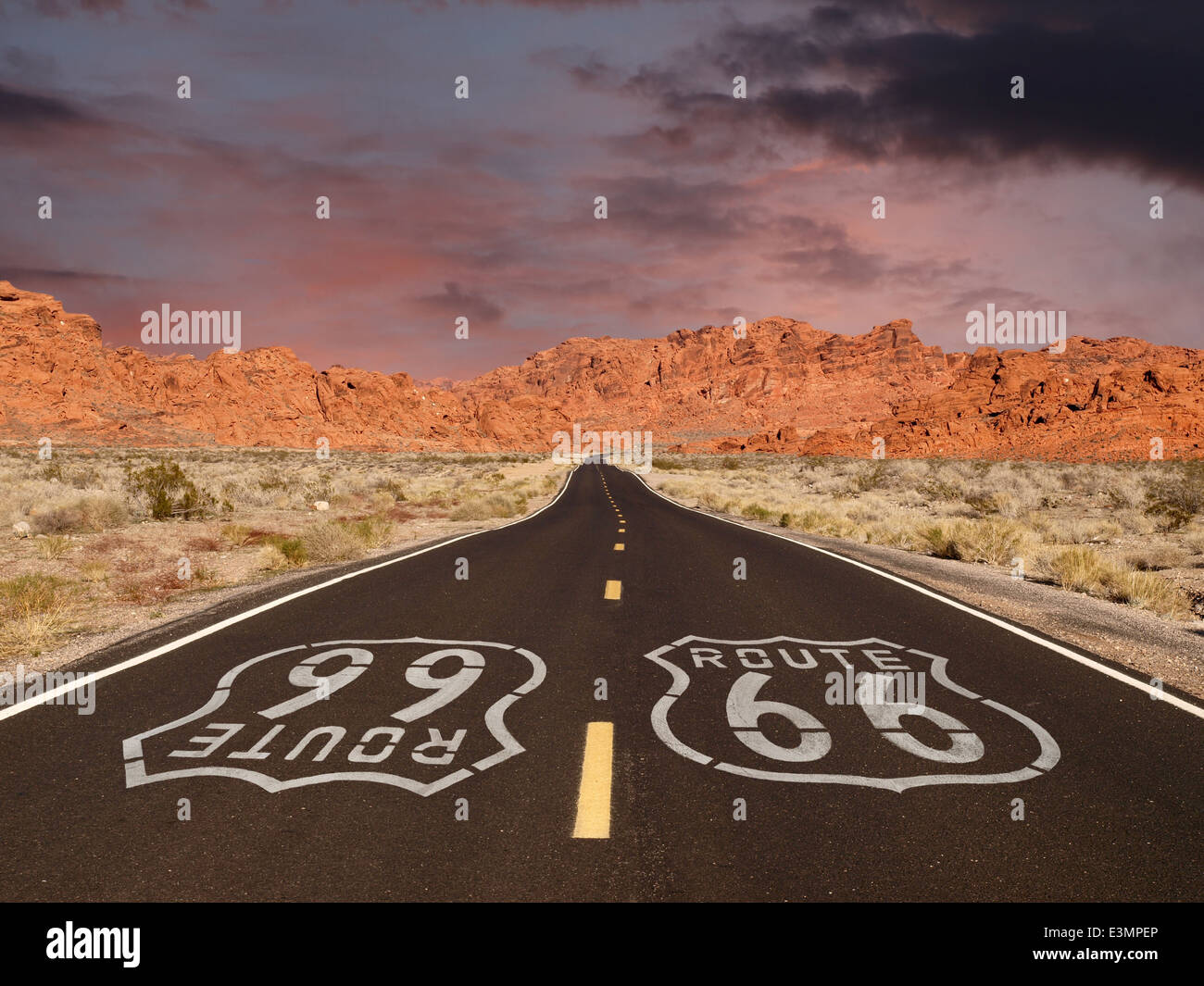 Route 66 pavement sign with Mojave desert red rock mountain sunset. - Stock Image