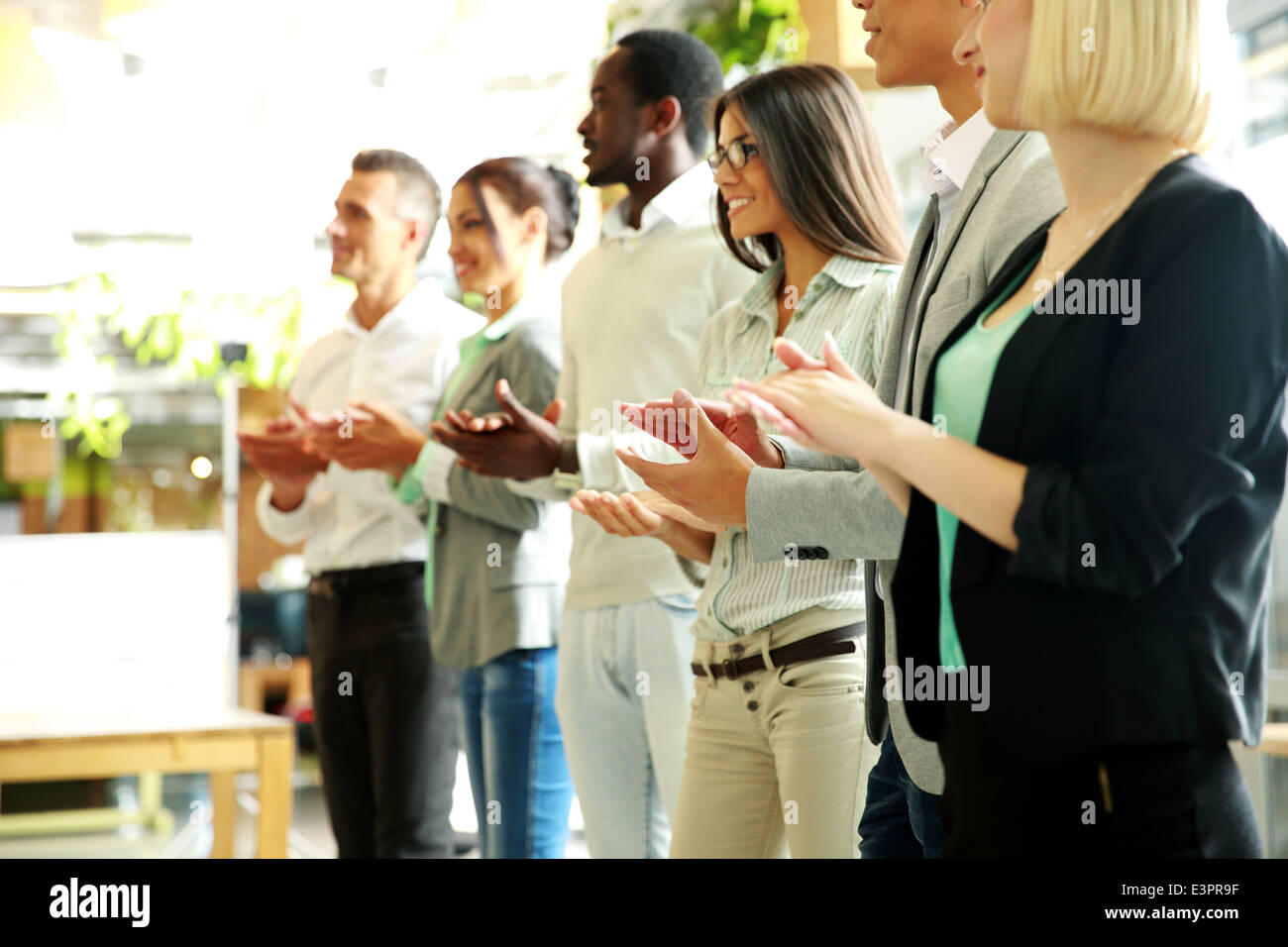 Group of cheerful business team applauding - Stock Image