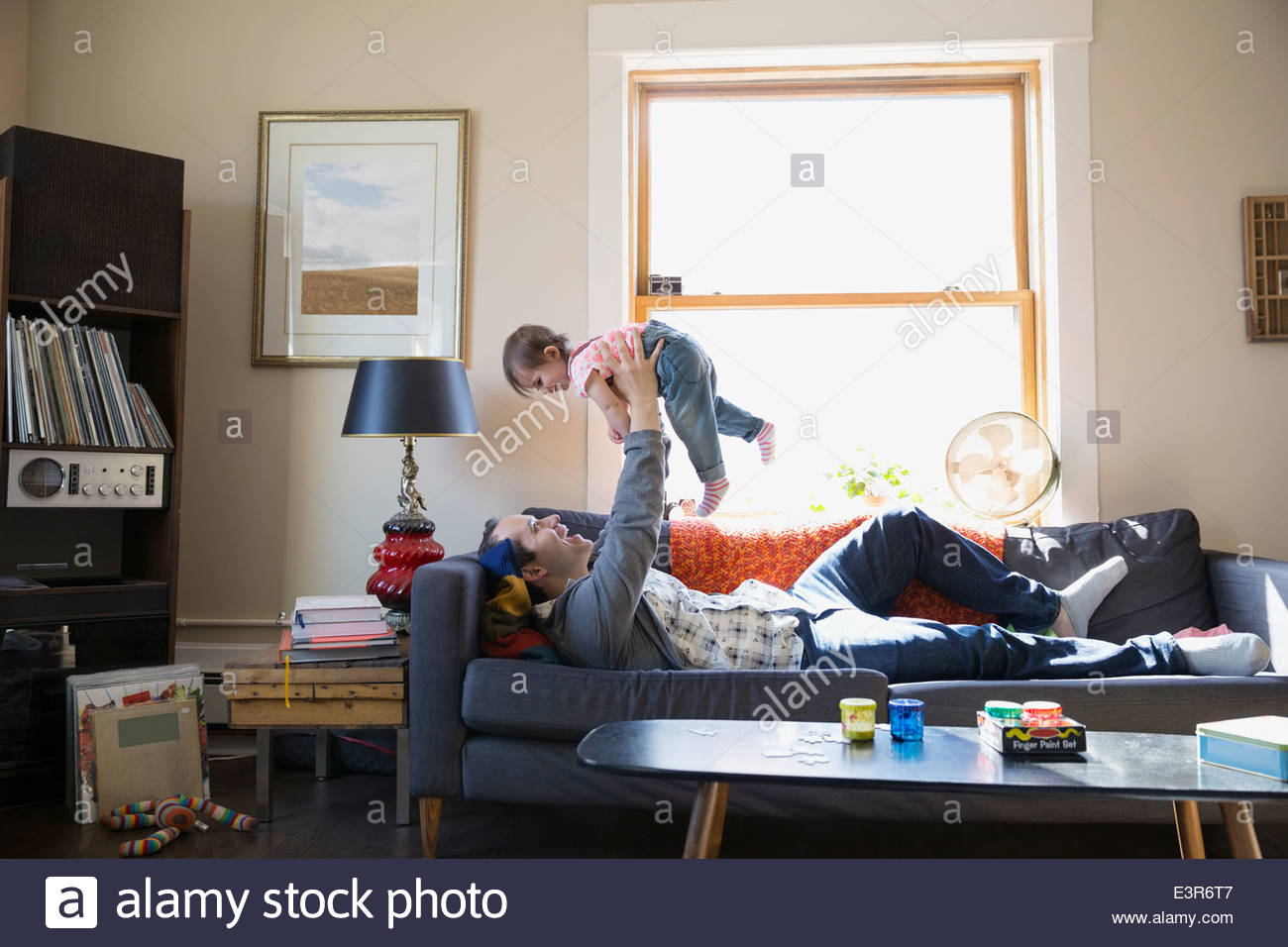 Father lifting baby daughter overhead on sofa - Stock Image