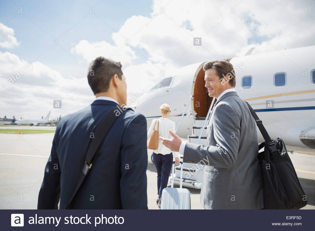 Businessmen talking on tarmac with corporate jet - Stock Image