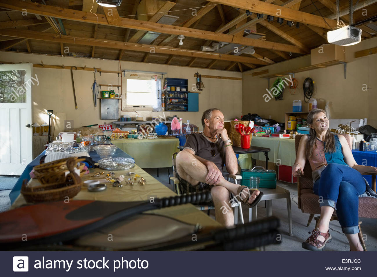 Couple sitting at garage sale - Stock Image