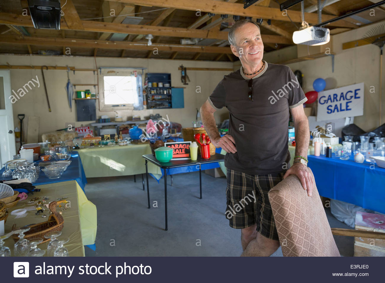 Confident man at garage sale - Stock Image