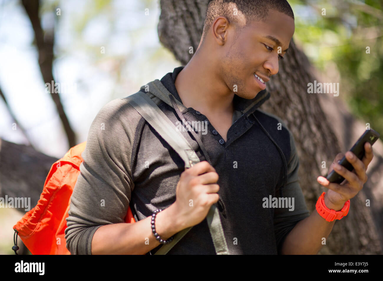 Young male hiker looking at smartphone - Stock Image