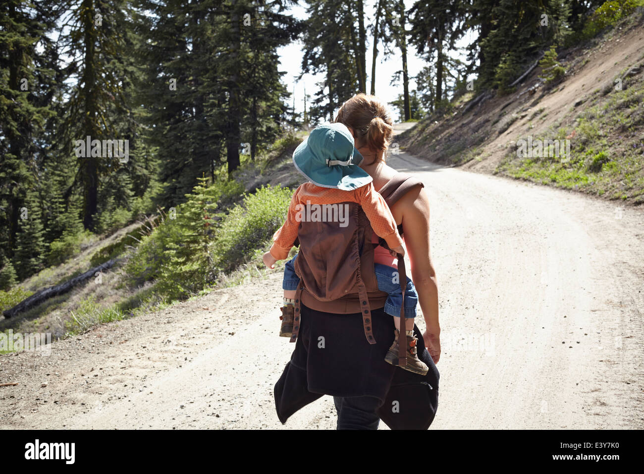 Rear view of mother carrying toddler in baby carrier - Stock Image