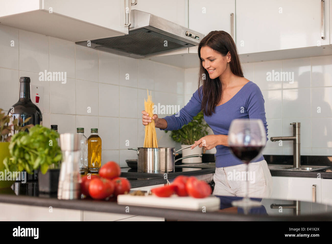 Young woman cooking spaghetti in kitchen - Stock Image