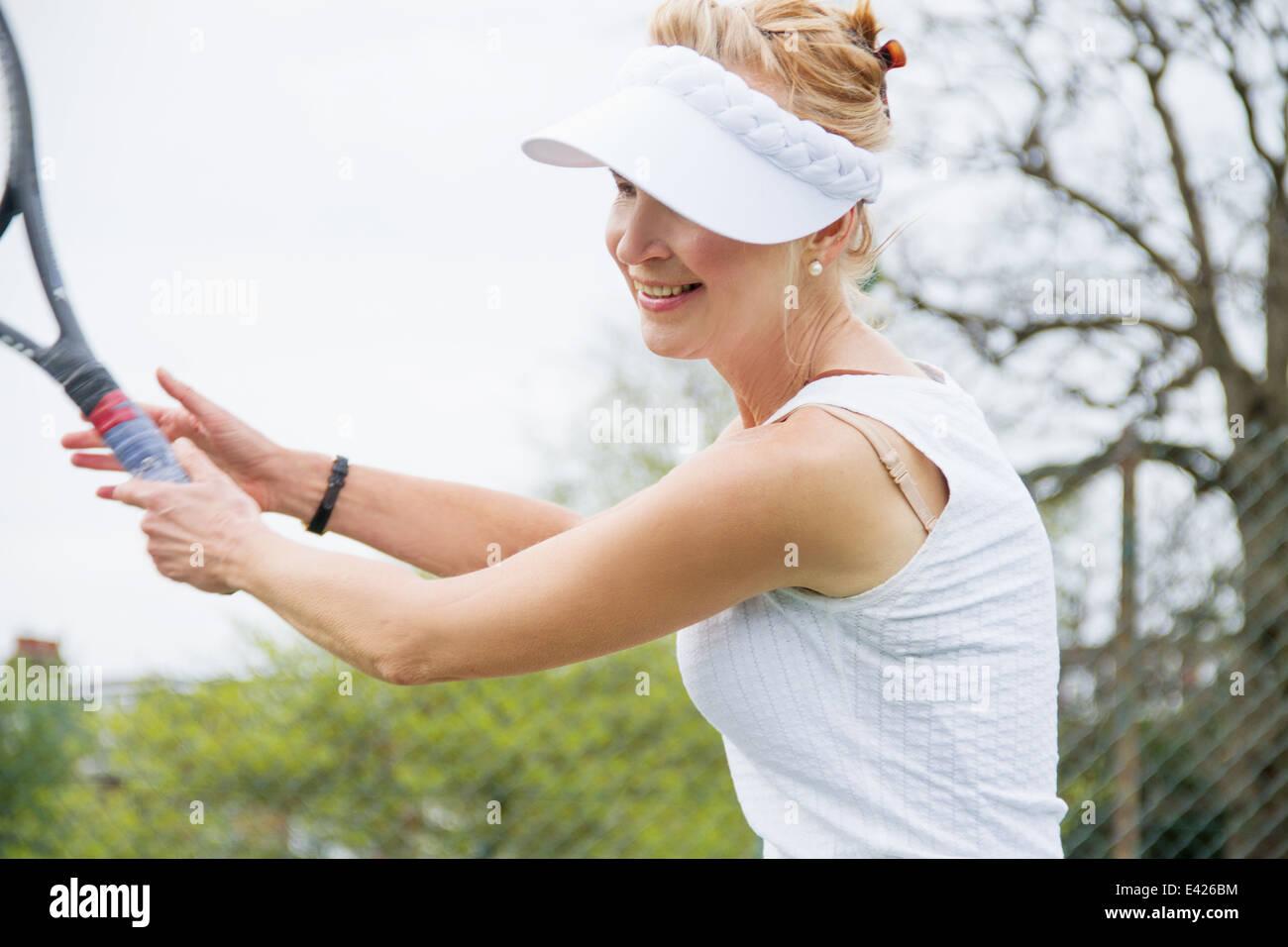 Mature female tennis player playing tennis - Stock Image