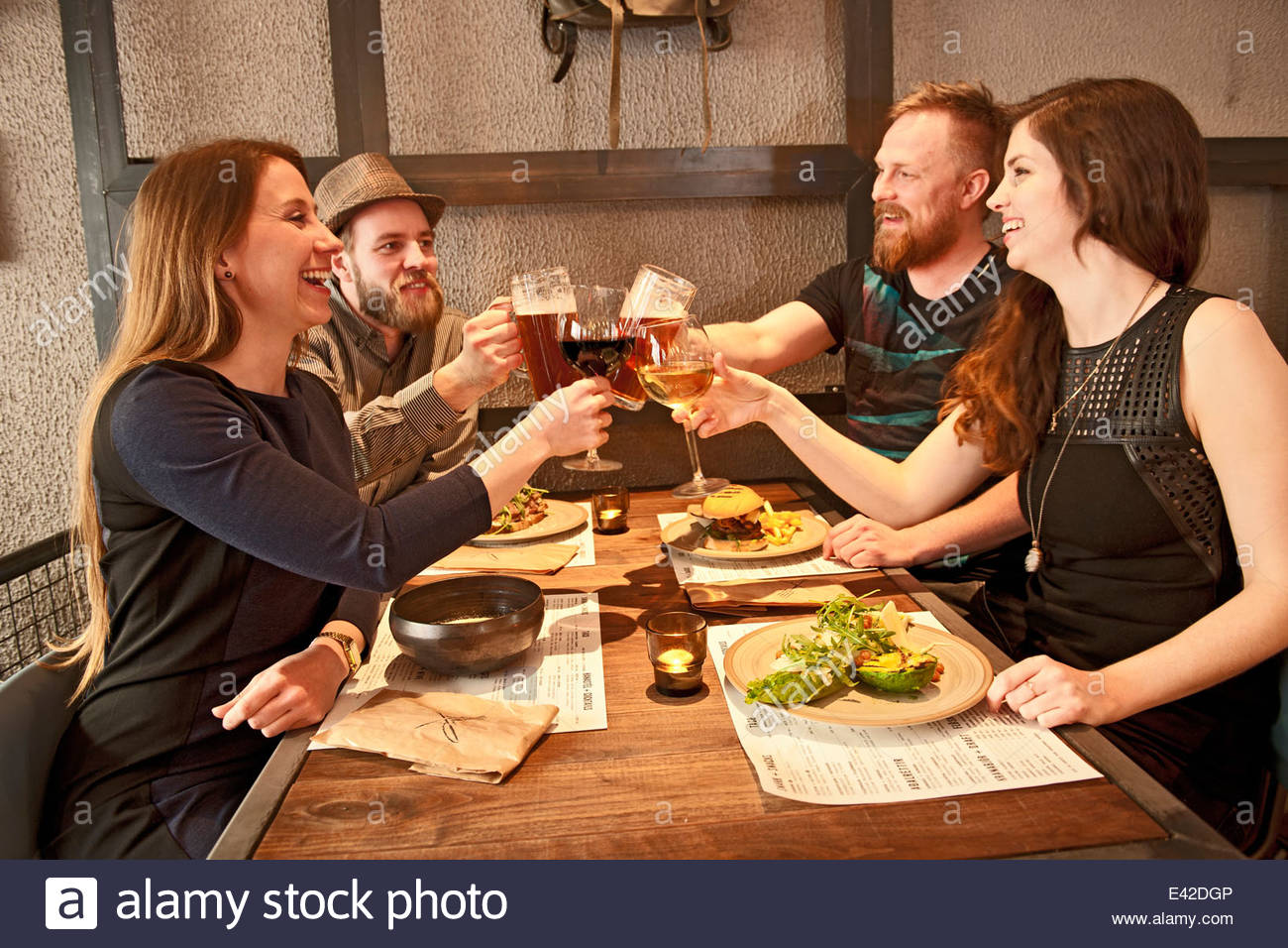 Friends toasting at hipster bar - Stock Image