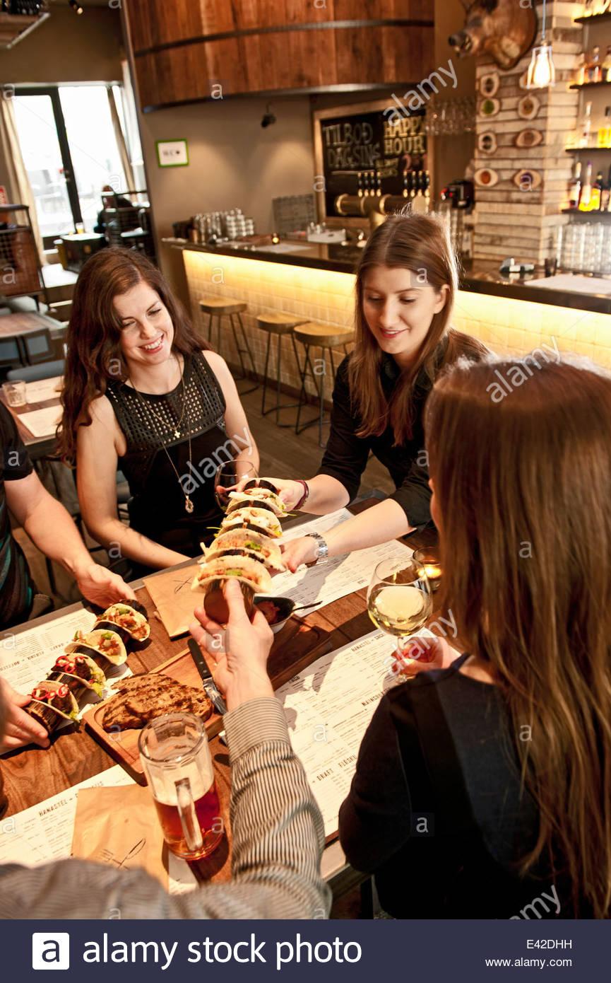 Waitress serving tacos at hipster bar - Stock Image
