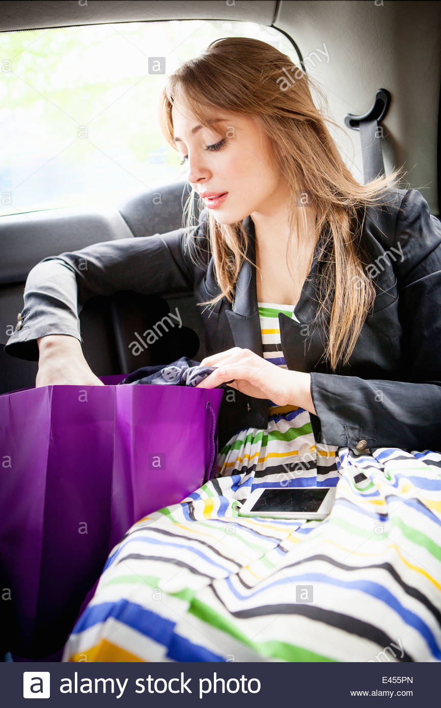 Young woman in back of taxi, looking in shopping bag - Stock Image
