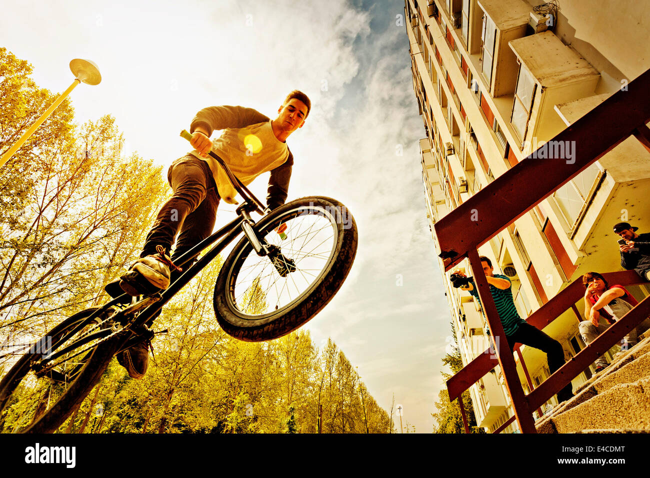 BMX biker performing a stunt over a railing - Stock Image