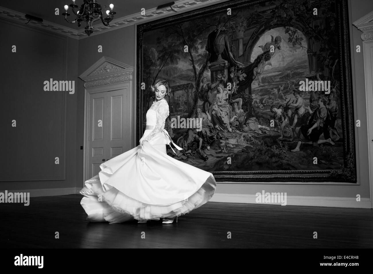 Wedding preparations, Bride dancing against old painting, Dorset, England - Stock Image