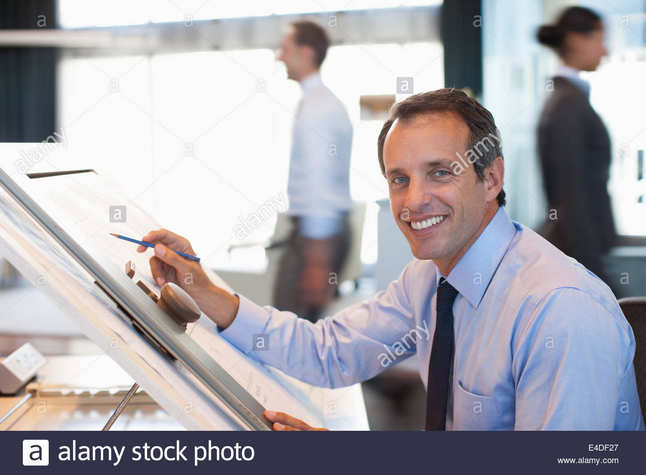 Architect drawing blueprint in office - Stock Image