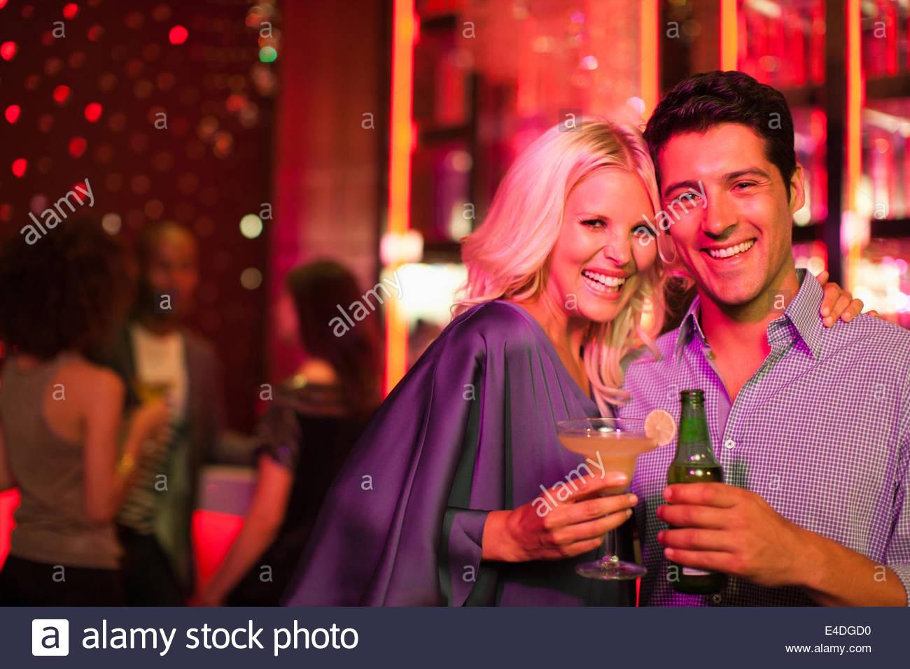 Couple holding drinks in nightclub - Stock Image