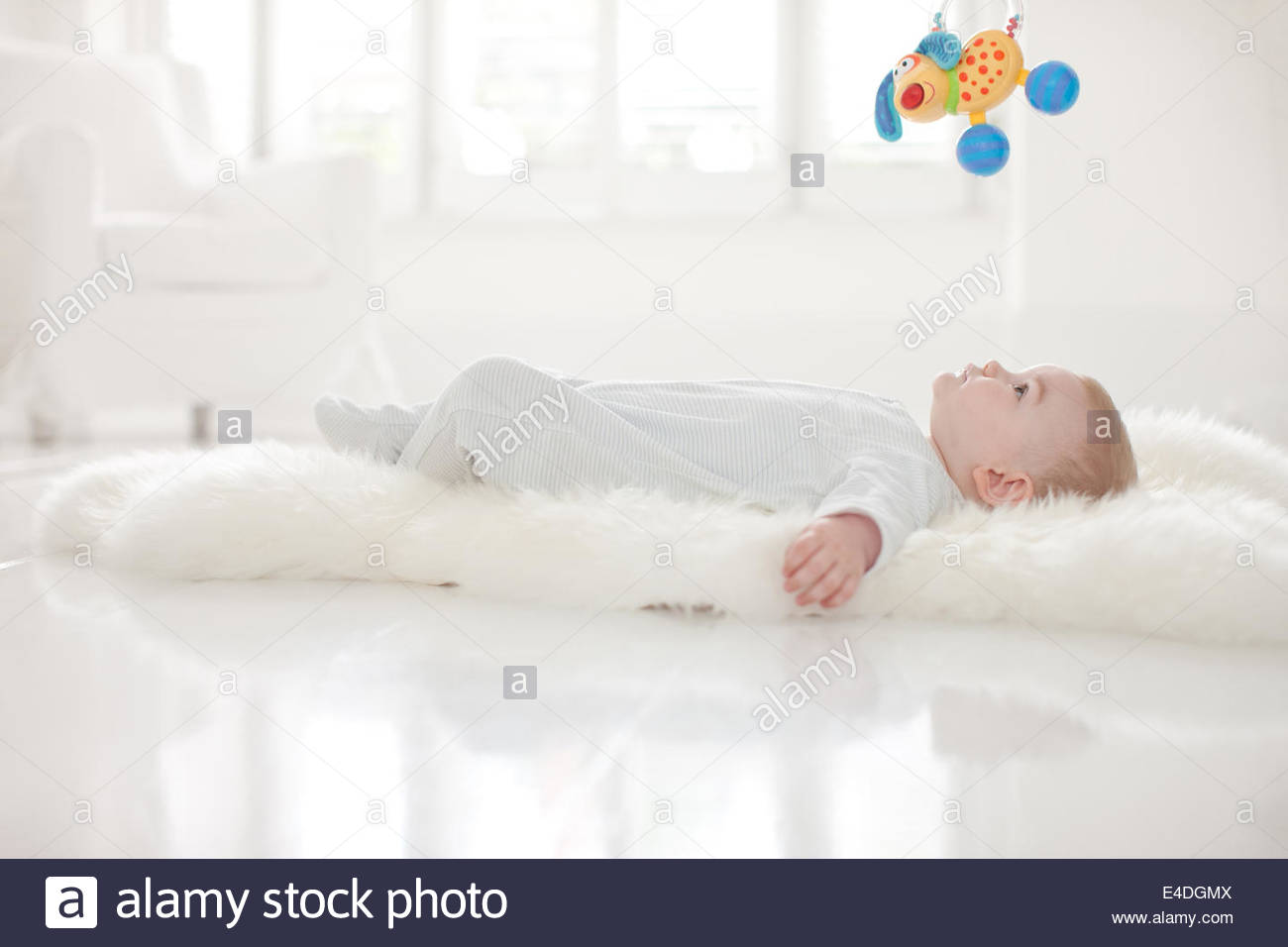 Baby on rug  for hanging toy overhead - Stock Image