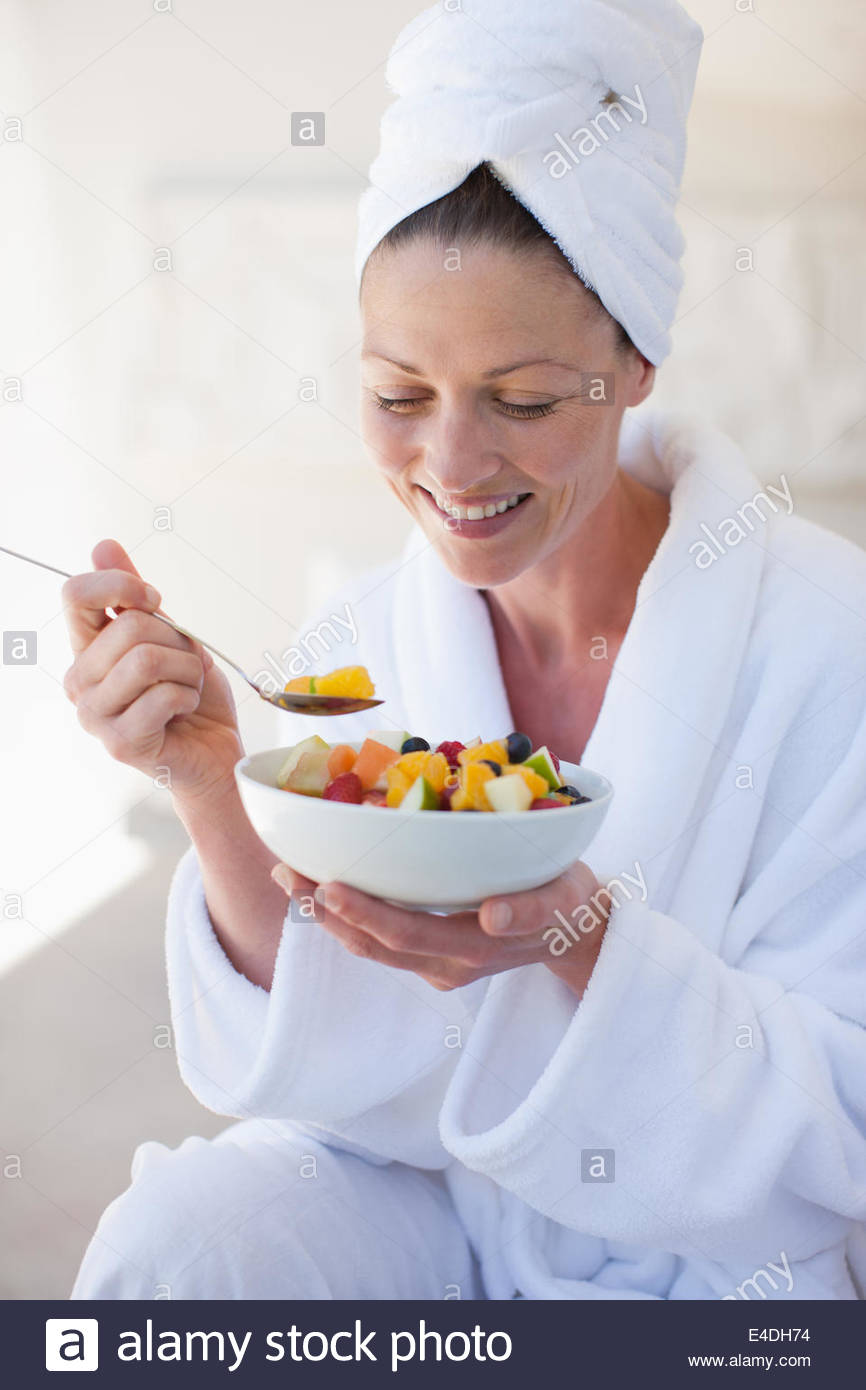 Woman in bathrobe eating bowl of fruit - Stock Image