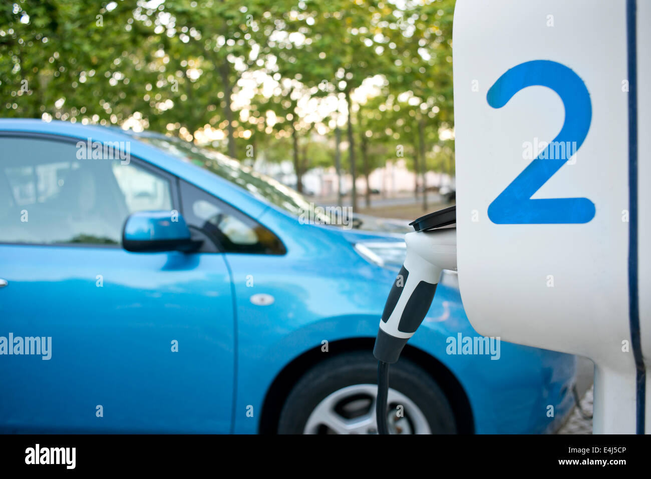 Electric car being recharged on a service station, in the street - Stock Image